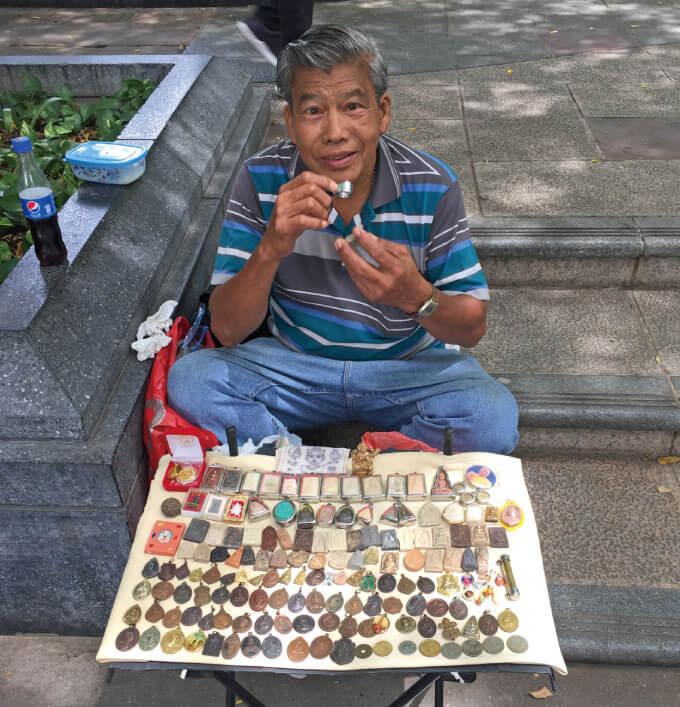路上でブッダが彫られた小石や小さな彫刻を売っている仏像屋